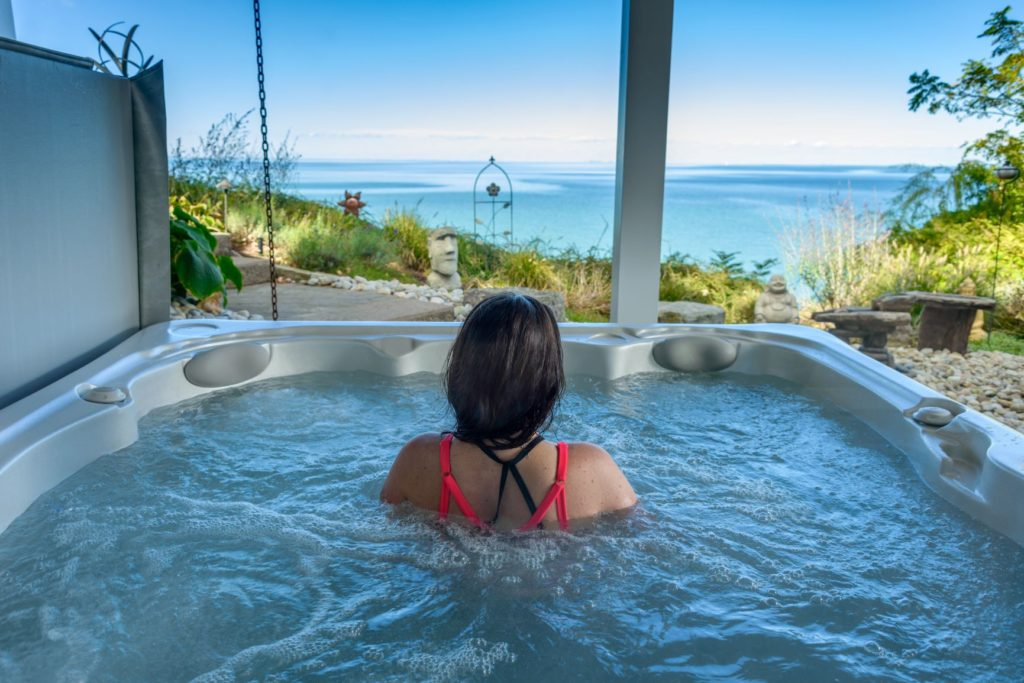 lady in serenity hot tub with view of sea